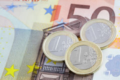 Münzen auf Banknote Stockfoto