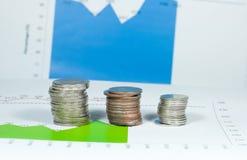 Münzen auf Diagramm- und Diagrammhintergrund des blauen Grüns Geld und fina Stockbild