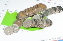 Münzen auf Diagramm- und Diagrammhintergrund des blauen Grüns Geld und fina Lizenzfreie Stockfotos