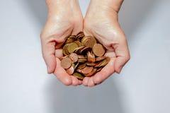 Münzen in den Händen Auf einem weißen und grauen Hintergrund lizenzfreie stockbilder