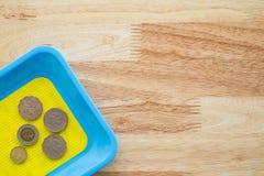 Münzen der japanischen Yen im bunten Münzenbehälter auf Holztisch Stockbilder