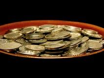 Münzen in der Suppeplatte Stockfotografie