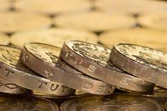 Münzen des britischen Pfunds auf einem Hintergrund des Geldes Stockfotos