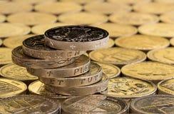 Münzen des britischen Pfunds in einem unordentlichen geschwankten Stapel Lizenzfreies Stockbild