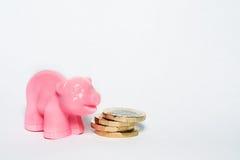 Münzen des britischen Pfunds und rosa Schwein Stockbilder