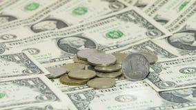 Münzen des russischen Rubels gegen einen USA-Dollarbanknotenhintergrund Stockfotos