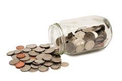 Münzen, die aus dem Glas XXXL heraus getrennt verschüttet werden Stockbilder