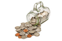 Münzen, die aus einen Glasbecher herauskommen Stockbild
