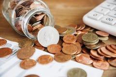 Münzen, die aus einer Glasflasche mit Rechnung und Taschenrechner heraus verschüttet werden Lizenzfreies Stockbild
