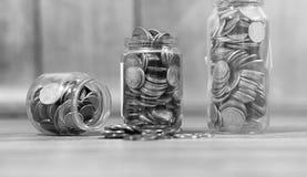 Münzen in einem Glas auf dem Boden Angesammelte Münzen auf dem Boden SAV Stockfoto