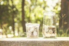 Münzen in einem Glasgefäß Stockfotos
