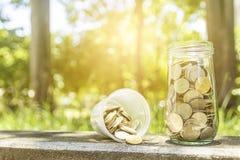 Münzen in einem Glasgefäß Stockbilder