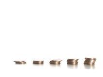 Münzen gegen weißen Hintergrund stockbild