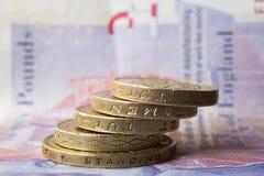 Münzen gestapelt auf einer zwanzig-Pfund-Anmerkung Stockfotografie