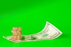 Münzen gestapelt in den Stäben auf Stapel des 100 Dollarscheins Stockfoto