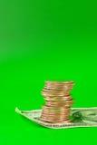 Münzen gestapelt in den Stäben, die auf 100 Dollarschein legen Stockbilder