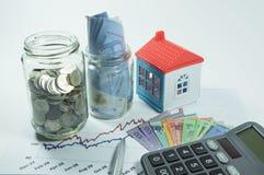 Münzen, Glas und Haus im Hintergrund Stockbilder