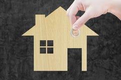 Münzen-Hand, die Hausikone von der hölzernen Beschaffenheit in der Natur als Symbol der Hypothek hält Stockfotos