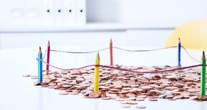 Münzen hinter farbigem Bleistiftzaun Stockbilder
