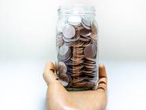 Münzen im Glasgefäß auf der hölzernen Hand lokalisiert auf weißem Hintergrund lizenzfreie stockbilder