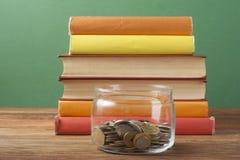 Münzen im Glasgefäß und im Stapel Büchern auf Holztisch Einsparungs-, financiai- und Bildungskonzept Lizenzfreie Stockfotografie