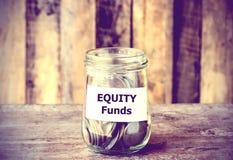 Münzen im Glasgeldglas mit Equity-Fonds-Aufkleber Stockfotografie