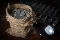 Münzen im Sack mit Taschenuhr und -abakus Lizenzfreie Stockfotos