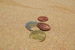 Münzen im Sand Stockfotografie