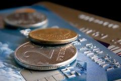 Münzen liegen auf Geldautomatenkarten gegen einen dunklen Hintergrund Lizenzfreies Stockbild