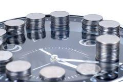Münzen mit der Anlage und Uhr, lokalisiert auf weißem Hintergrund Stockfotos