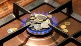Münzen sind auf einem brennenden Gasbrenner Gasreform setzt Leute auf ihre Knie stock video footage