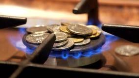 Münzen sind auf einem brennenden Gasbrenner Nicht genügend Geld, zum für Gas zu zahlen stock footage