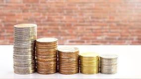 Münzen stapeln auf Backsteinmauerbeschaffenheitshintergrund Stockfoto