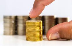 Münzen stapeln und übergeben ausgewählte goldene Münze auf der weißen Tabelle Stockfotos