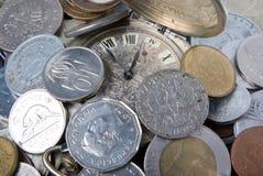 Münzen und alte Uhr Stockbilder