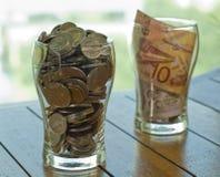 Münzen und Anmerkungsgetränk für Nächstenliebe Stockfotos