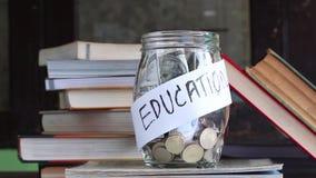 Münzen und Banknote in einem Glasgefäß gesetzt auf das Lehrbuch stock video footage
