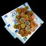 Münzen und Banknoten auf einem schwarzen Hintergrund Lizenzfreie Stockfotos