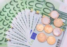 Münzen und Banknoten im Hintergrund Stockfotografie