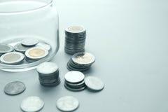 Münzen und Glasglas Stockfoto