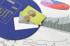 Münzen und Kreditkarten auf einem Dokument mit einigen Grafiken stockbilder