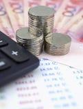 Münzen und Taschenrechner auf dem Hintergrund der chinesischen Währung und der Rechnungen Stockfotografie