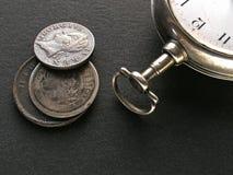 Münzen und Uhr lizenzfreies stockfoto