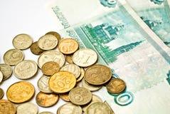Münzen und weiches Geld Stockfoto
