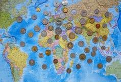 Münzen von verschiedenen Ländern auf dem Weltkartehintergrund Lizenzfreies Stockbild