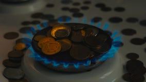 Münzen von verschiedenen Ländern auf einem Gasbrenner Symbol von zunehmenden Kraftstoffpreisen stock footage