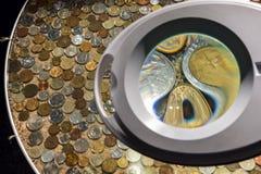 Münzen von verschiedenen Ländern durch eine Lupe Lizenzfreie Stockfotos