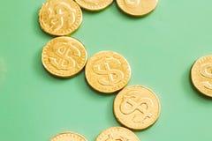 Münzendollar auf einem grünen Hintergrund Feder, Brillen und Diagramme Lizenzfreies Stockbild
