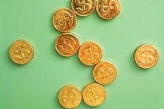 Münzendollar auf einem grünen Hintergrund Feder, Brillen und Diagramme Lizenzfreie Stockfotos