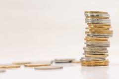 Münzenstapel auf weißem Hintergrund lizenzfreie stockfotos